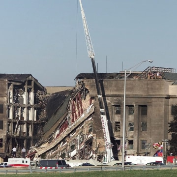 Image: USA FLAG HANGS AT IMPACT AREA ONE DAY AFTER HIJACKED JET CRASHED INTO PENTAGON