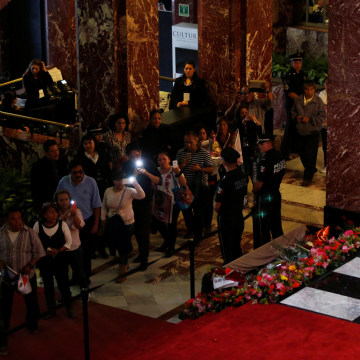 Image: Fans take pictures of the urn containing the ashes of Juan Gabriel during his second day homage in the Bellas Artes Palace in Mexico City