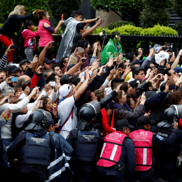 Image: Fans take pictures of the hearse carrying the ashes of the late Mexican singer Juan Gabriel as its arrives at the official tribute outside the Bellas Artes Palace in Mexico City, Mexico