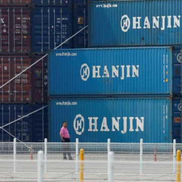 A man stands in front of shipping containers at the Hanjin Shipping container terminal at Incheon New Port in Incheon