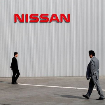 Men walk past a Nissan Motor Co logo at the company's global headquarters in Yokohama