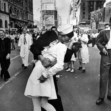 A jubilant American sailor clutching a white-unifo
