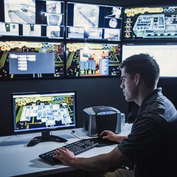 Hispanic security guard watching monitors in control room