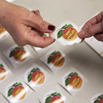 Image: A poll worker hands a sticker to a voter