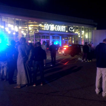 Image: People stand outside the scene of a stabbing at the Crossroads Center mall in St. Cloud, Minnesota