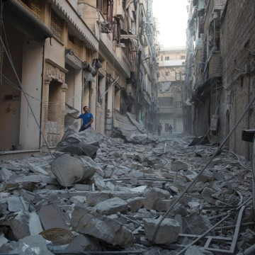 Image: A man stands in rubble in Aleppo