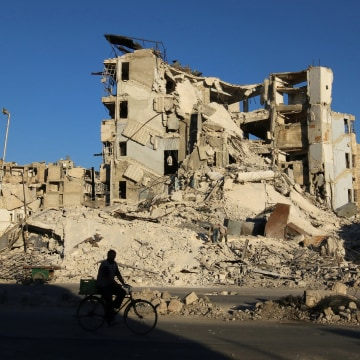 Image: A man rides a bicycle past damaged buildings in the rebel-held Tariq al-Bab neighborhood of Aleppo