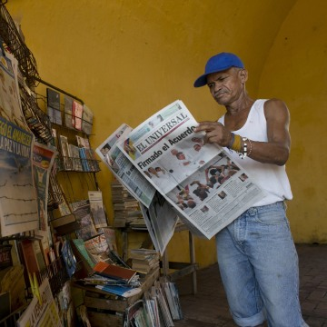 """Saul Lambis reads a newspaper carrying the headline in Spanish """"Agreement Signing"""" in Cartagena, Colombia, Tuesday, Sept. 27, 2016."""