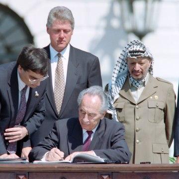 Image: Shimon Peres signs historic Israel-PLO Oslo Accords.