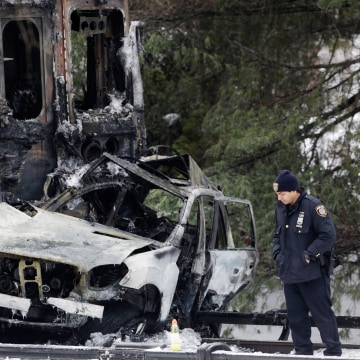 Image: A police officer looks at an SUV that was crushed at the front of a Metro-North train