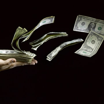 US Paper Money Flying out of Man's Hand