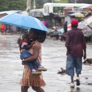 Image: A woman carrying a child walks in the rain triggered by Hurricane Matthew