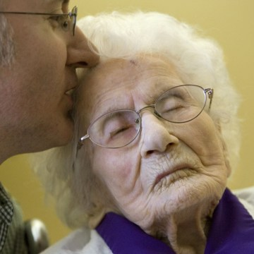 Image: Besse Cooper, 114, right, receives a kiss from her grandson