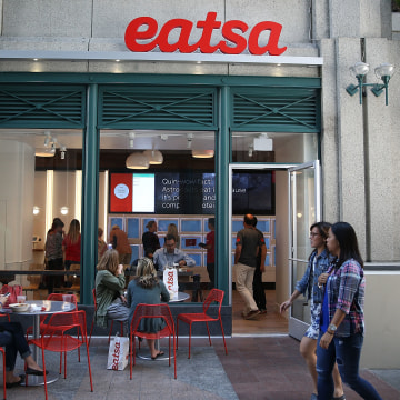 Image: People walk by eatsa, a fully automated fast food restaurant