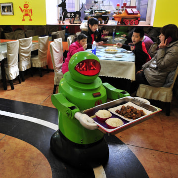 Image: Robots deliver dishes to customers at a Robot Restaurant in Harbin
