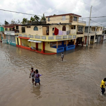 Image: People walk in a flooded area after Hurricane Matthew in Les Cayes