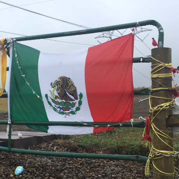 Mexican flag draped across a rusty gate where protesters are working to stop the construction of the Dakota Access Pipeline.