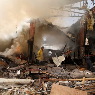 Image: Firefighters at the community hall where Saudi-led warplanes struck a funeral Saturday.