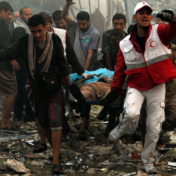 Image: Yemeni rescue workers carry a victim on a stretcher amid the rubble of a the destroyed building.