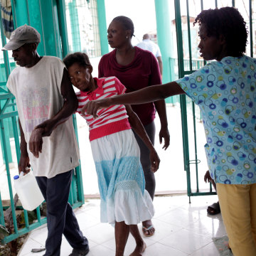 Image: A woman with symptoms of cholera is carried into the hospital at Port-a-Piment, Haiti