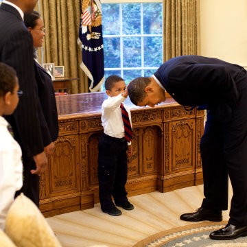 Image: President Barack Obama bends over so the son of a White House staff member can pat his head during a visit to the Oval Office