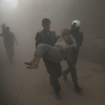 Image: Civil defense members carry an injured man after an air strike in the rebel-held Douma neighbourhood of Damascus