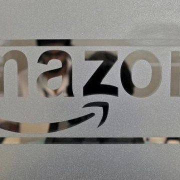 Employees of Amazon India are seen behind a glass bearing the company's logo inside its office in Bengaluru