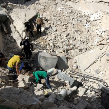 Image: First responders search a site damaged in an airstrike