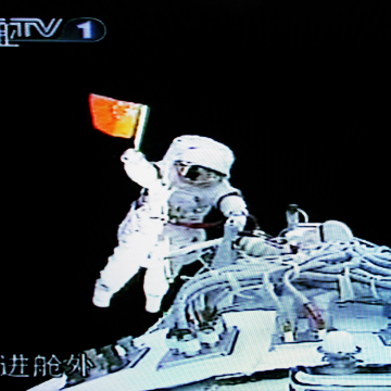 Image: Zhai Zhigang waves a small Chinese flag shortly after climbing out of the Shenzhou VII spacecraft