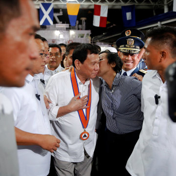 Image: Philippines President Rodrigo Duterte is kissed by a woman in Manila