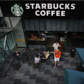 Customers walk out of a Starbucks coffee store in Shanghai