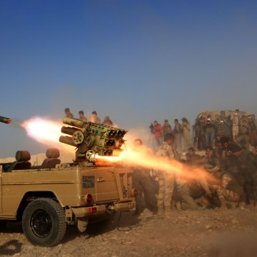Image: Iraqi Kurdish peshmerga fighters fire a multiple rocket launcher