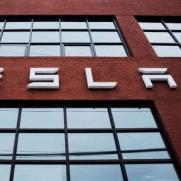 A Tesla logo hangs on a building outside of a Tesla dealership in New York