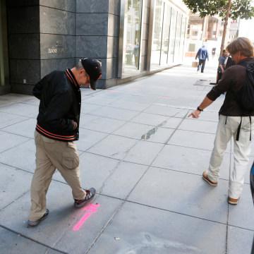 Image: Pedestrians inspect cracks near the sinking Millennium Tower in San Francisco, California