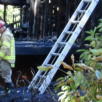 Image: A firefighter inspects the scene of the fire
