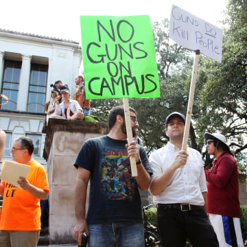Image: Students holds signs as they protest a campus carry law