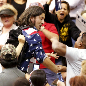 Image: A member of the audience throws a punch at a protester as Republican Presidential candidate Donald Trump speaks