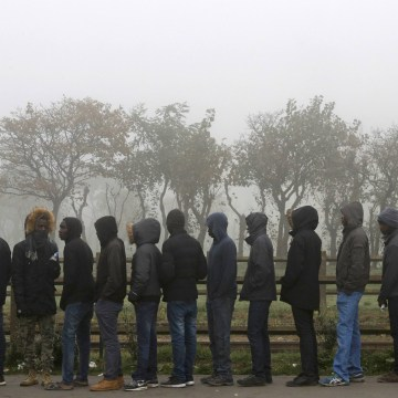 "Image: Migrants line up on the third day of evictions from the ""Jungle"" in Calais, France."