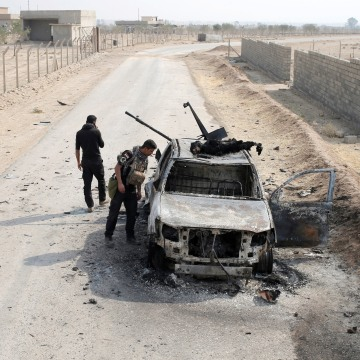 Image: Iraqi special forces soldiers looks at a destroyed Islamic State vehicle in a village near Mosul