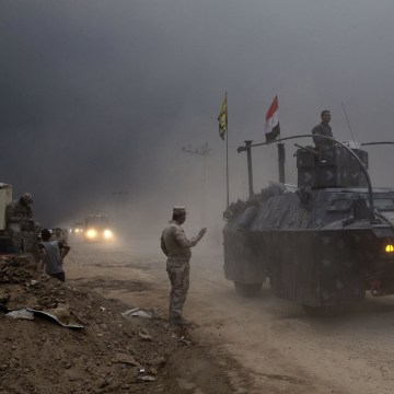 Image: An Iraqi Federal Police vehicle passes through a checkpoint in Qayara