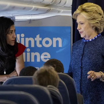 Image: Clinton speaks with senior aide Huma Abedin aboard her campaign plane