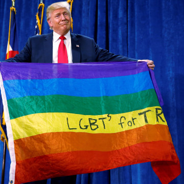 "Image: Republican presidential nominee Donald Trump holds up a rainbow flag with ""LGBT's for TRUMP"" written on it at a campaign rally in Greeley"