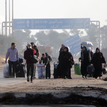 Image: Syrians carry their belongings as they leave Aleppo on Oct. 30, 2016