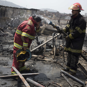 Firemen cool off amid charred debris following an early morning fire that destroyed hundreds of homes, in the shantytown known as Cantagallo, in Lima, Peru, Friday, Nov. 4, 2016.