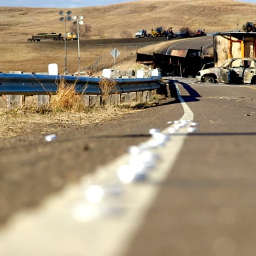 Image: Unlit candles line the road to the Backwater Bridge on North Dakota Highway 1806