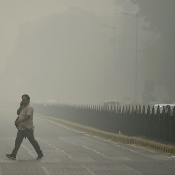 Image: An Indian pedestrian walks through heavy smog in New Delhi, Sunday.
