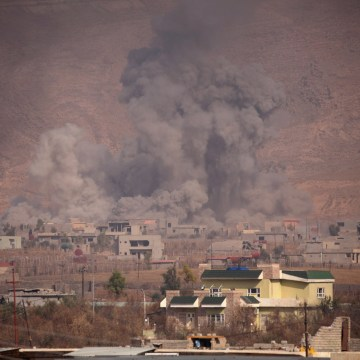 Image: Smoke rises during clashes between Peshmerga forces and ISIS militants in Bashiqa, Iraq