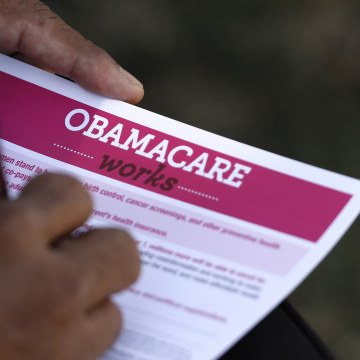 Image: A man fills out an information card during an Affordable Care Act outreach event hosted by Planned Parenthood for the Latino community in Los Angeles, California