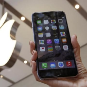 A woman holds up the iPhone 6 Plus at the Apple Store in Tokyo