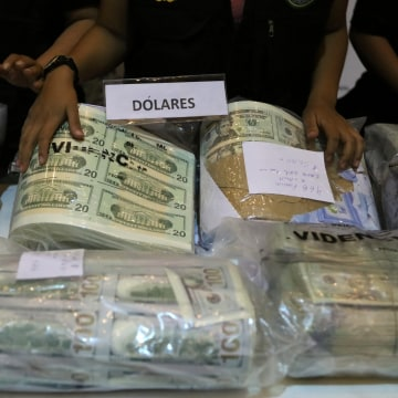 Image: Police officers display seized counterfeit U.S. and Nuevos Soles bills at a news conference in Lima, Peru